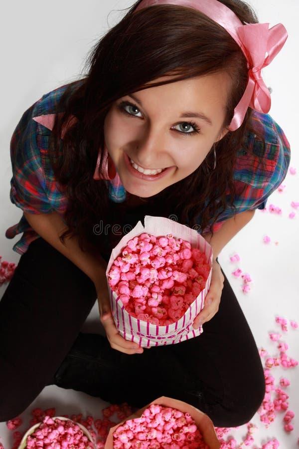 Het meisje van de tiener en roze popcorn stock foto