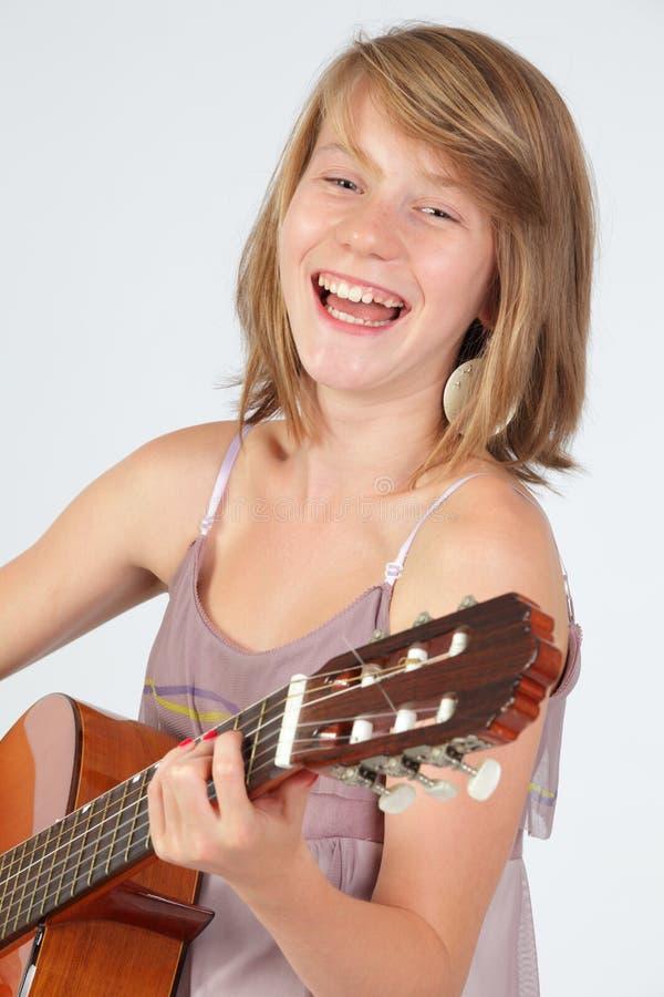 Het meisje van de tiener het spelen gitaar stock foto's