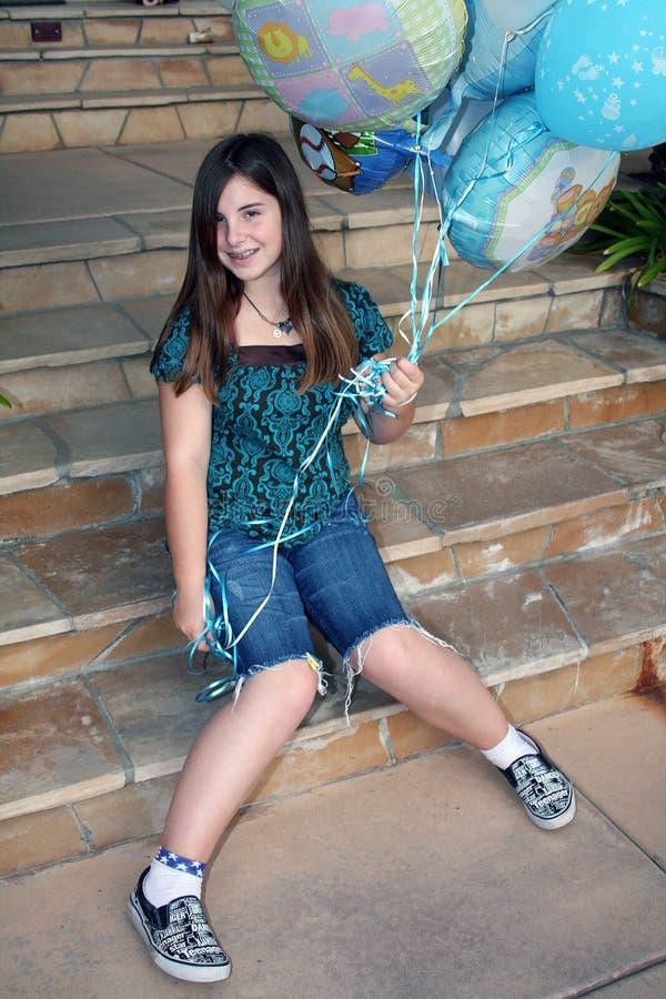 Het meisje van de tiener houdt bos van ballons stock foto