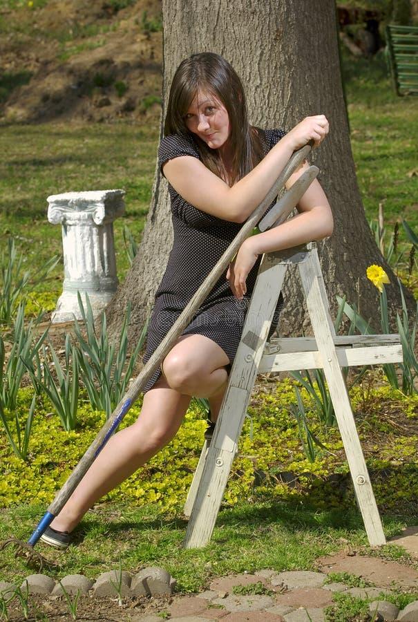 Het meisje van de tiener met tuinhulpmiddelen en ladder stock afbeelding