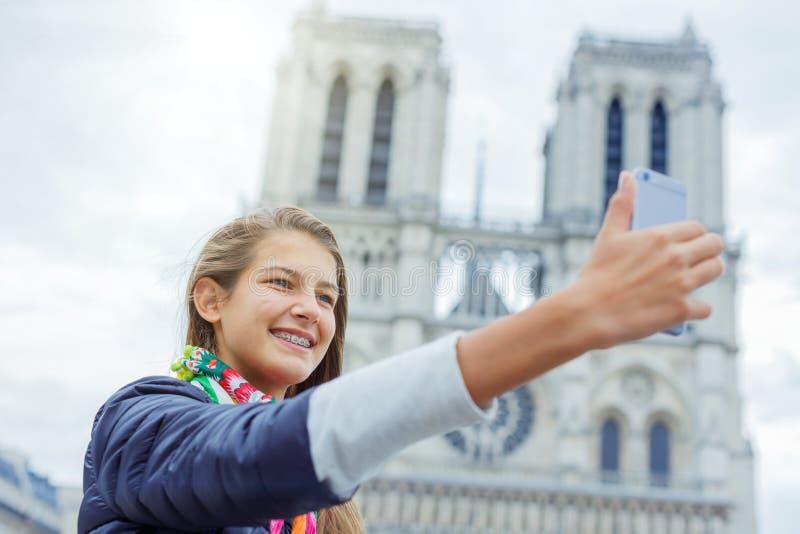 Het meisje van de tienertoerist neemt selfie met kathedraal van Notre Dame de Paris frankrijk stock fotografie