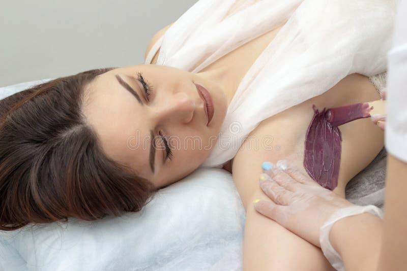 Het meisje van de wasontharing doet het in de was zetten procedure voor underarm die het mooie meisje liggen op laag in kuuroordc royalty-vrije stock afbeeldingen