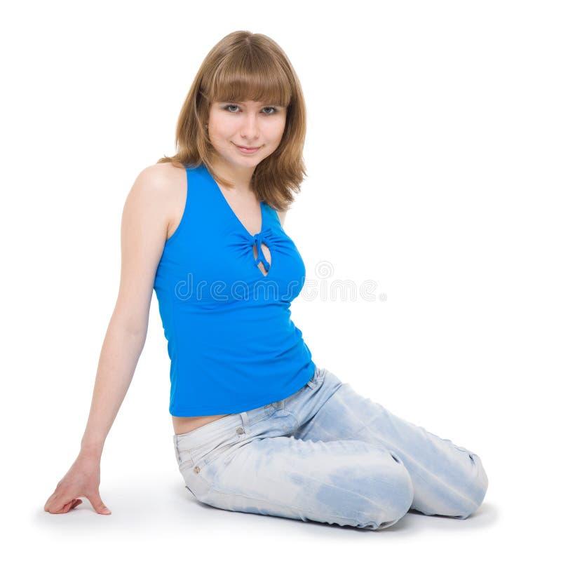 Het meisje van de zitting in jeans. stock afbeeldingen