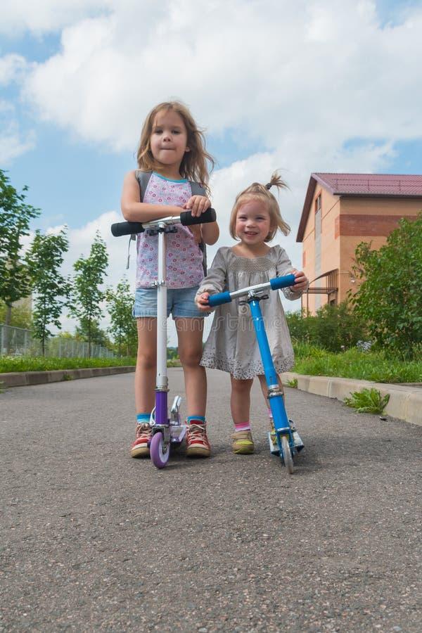 Het meisje van de de zomerdag, kind op autoped stock foto's
