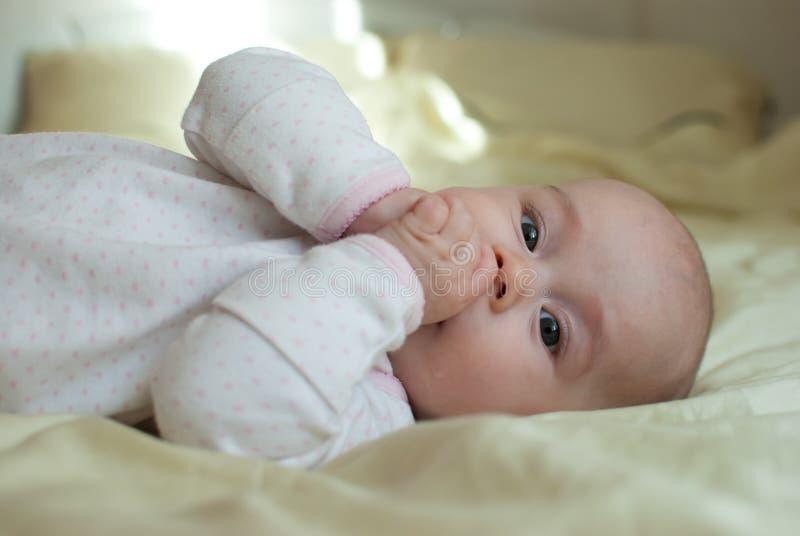 Het meisje van de zuigelingsbaby in bed royalty-vrije stock afbeelding