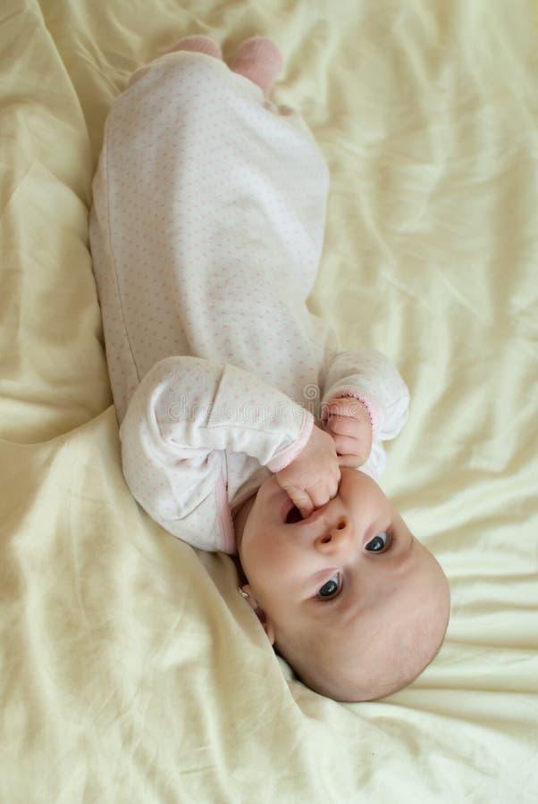 Het meisje van de zuigelingsbaby in bed stock fotografie