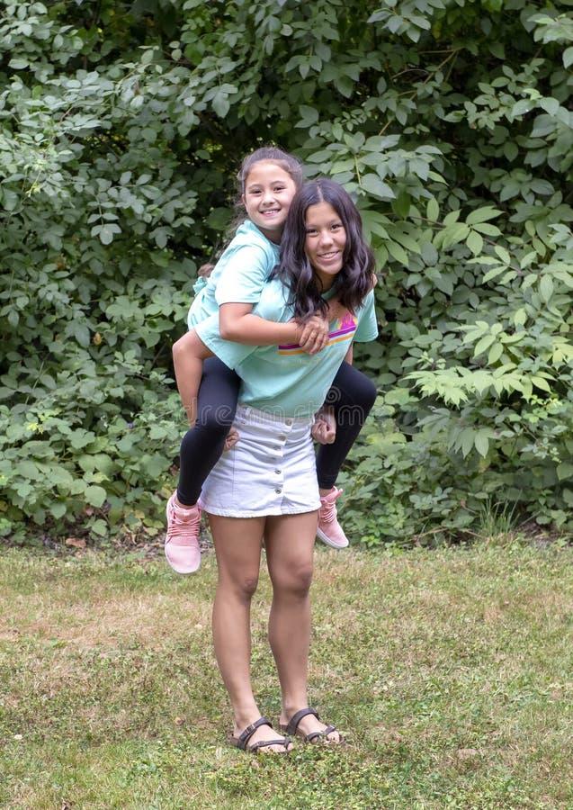 Het meisje van dertien éénjarigenamerasian met haar de zuster van tien éénjarigenamerasian het berijden op de rug in Washinton-Pa stock afbeelding