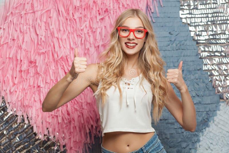 Het meisje van het gelukblonde in rode glazen, die duimen tonen, het kijken stock afbeelding