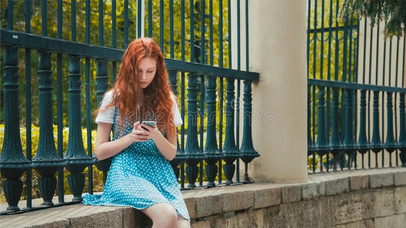 Het meisje van het gemberroodharige onderzoekt de telefoon royalty-vrije stock foto's