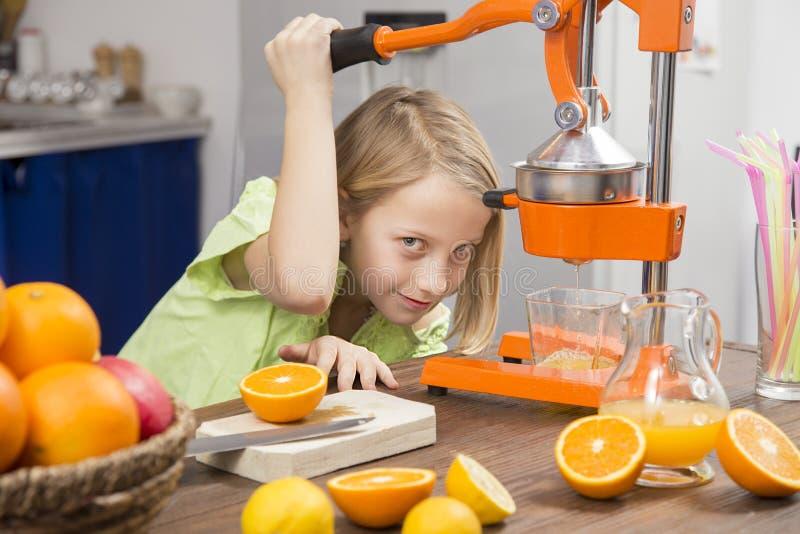 Het meisje van het glimlachblonde maakt jus d'orange stock foto's