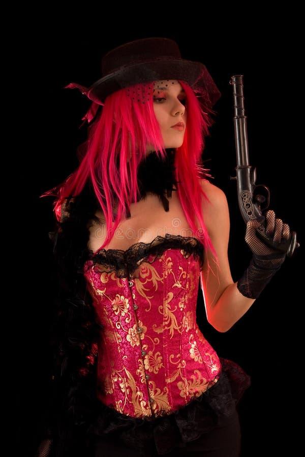 Het meisje van het cabaret in het roze kanon van de korsetholding stock foto