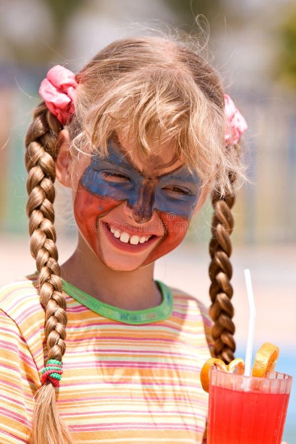 Het meisje van het kind met verf op gezicht drinkt sap. stock fotografie