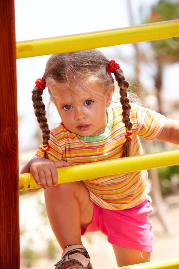 Het meisje van het kind op ladder in speelplaats. stock afbeelding