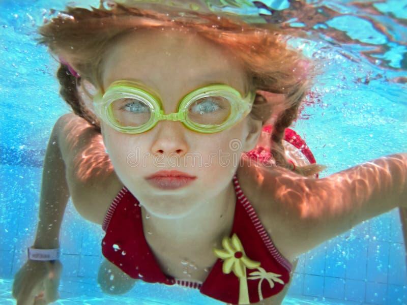 Het meisje van het kind zwemt onderwater in pool. royalty-vrije stock afbeelding