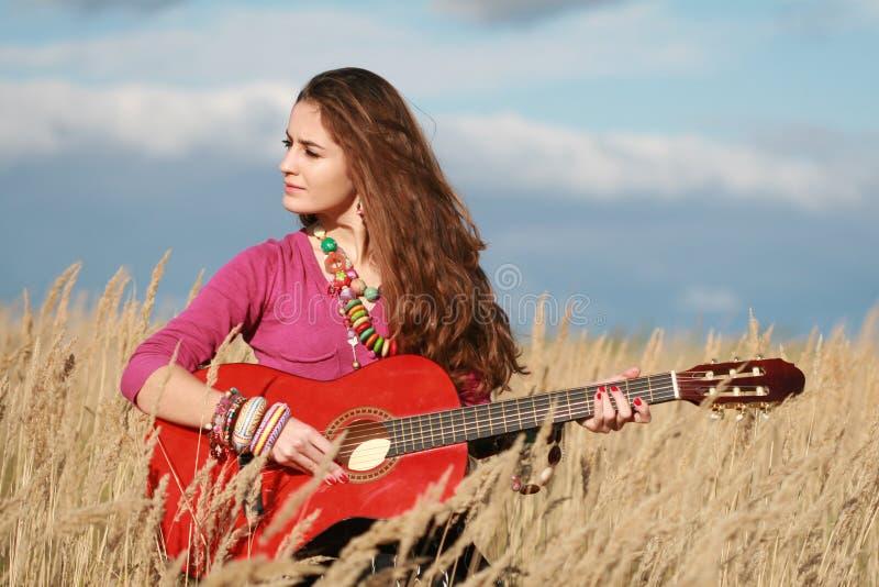Het meisje van het land het spelen gitaar stock foto's