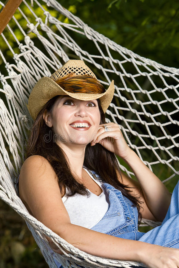 Het meisje van het landbouwbedrijf in een hangmat stock afbeelding