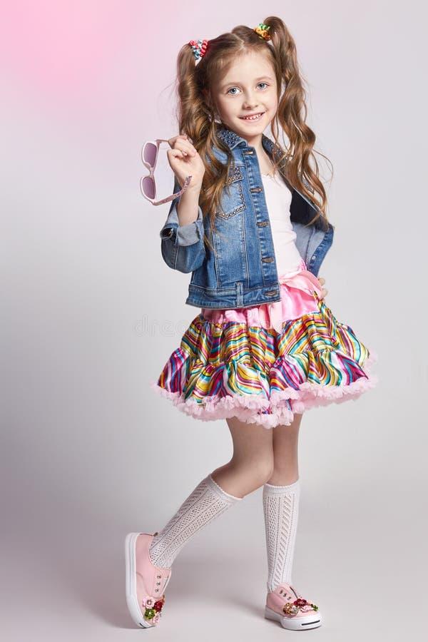 Het meisje van het manierroodharige in een feestelijke en uitrusting die stellen glimlachen Studiofoto op licht gekleurde achterg stock foto's