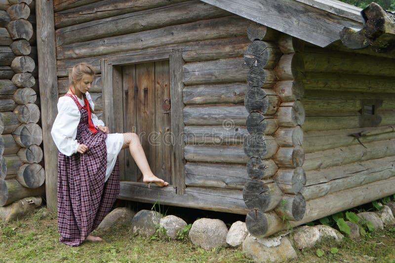 Het meisje van het oude dorp, die zich op een gesloten loods bevinden en waargenomen de pijn zijn been royalty-vrije stock afbeeldingen