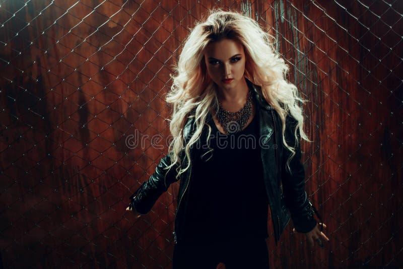 Het meisje van het rots` n ` broodje, jonge mooie vrouw danst in donkere steeg, tegen het omheiningsnetwerk stock foto's