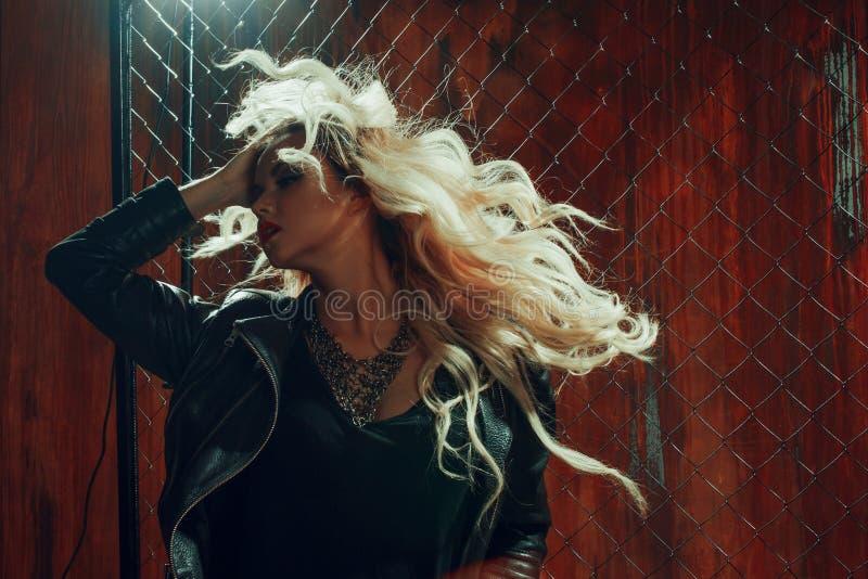 Het meisje van het rots` n ` broodje, jonge mooie vrouw danst in donkere steeg, tegen het omheiningsnetwerk royalty-vrije stock foto's