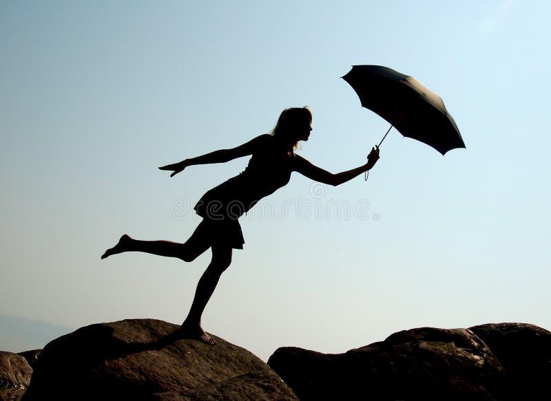 Het meisje van het silhouet met paraplu stock afbeelding