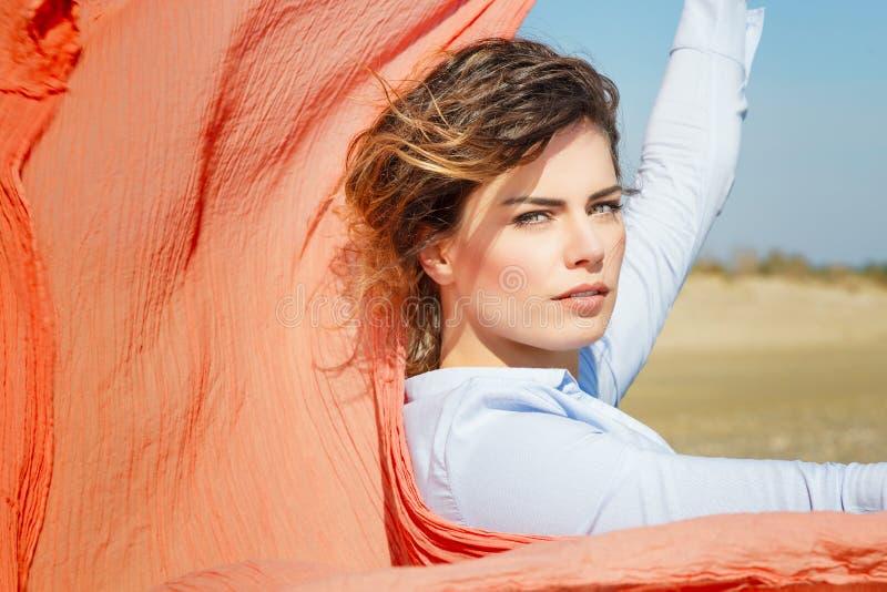 Het Meisje van het windhaar met Rode Sjaal op de wind stock foto