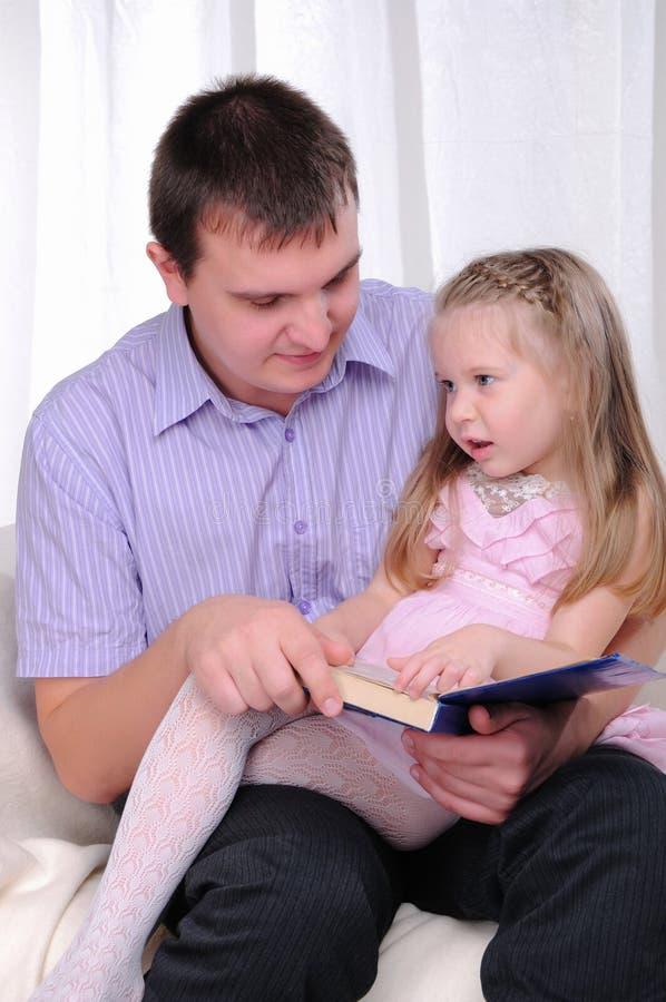 Het meisje van Ittle zit op de overlapping van zijn vader stock afbeeldingen