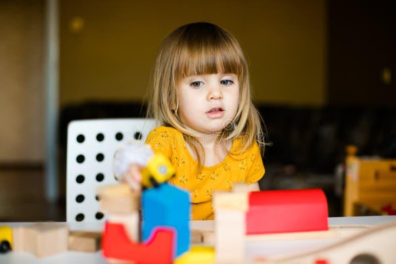 Het meisje van Nice in het gele kleding spelen met kleurrijke bakstenen stock afbeelding