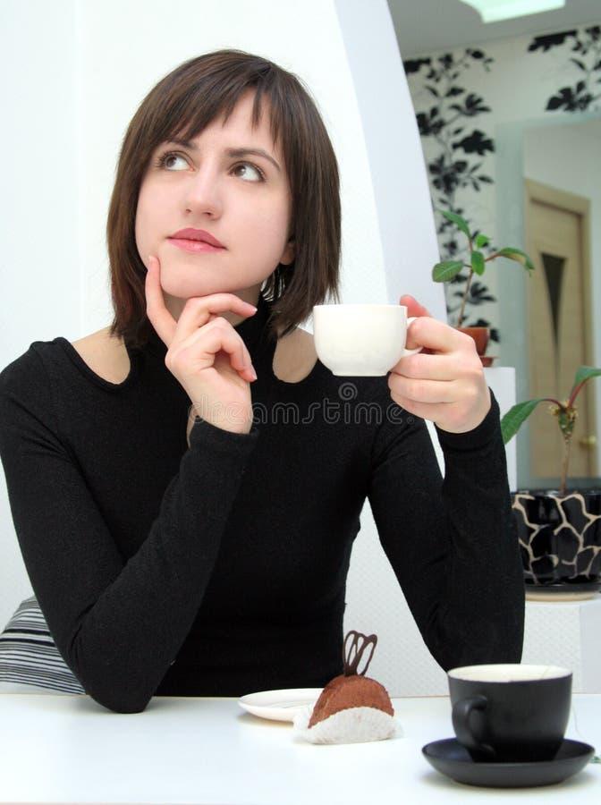 Het meisje van Nice het drinken koffie in een koffie stock foto