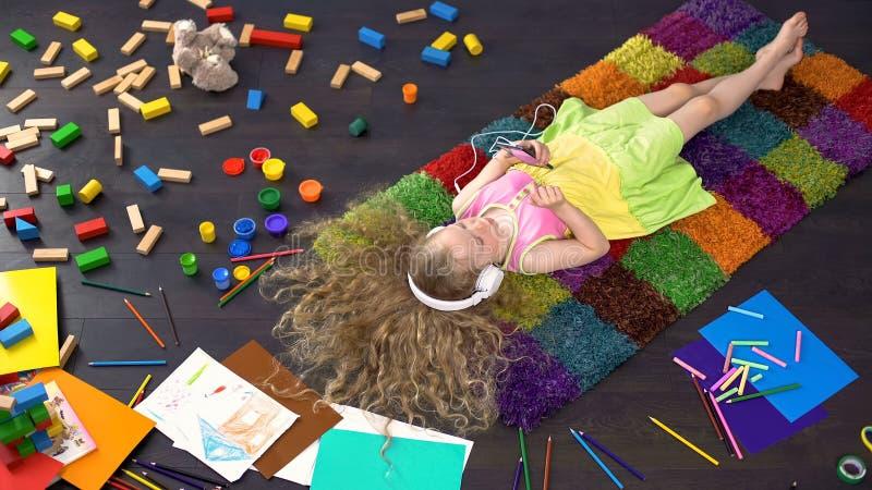 Het meisje van Nice in hoofdtelefoon die op vloer liggen en aan muziek, smartphone luisteren stock fotografie
