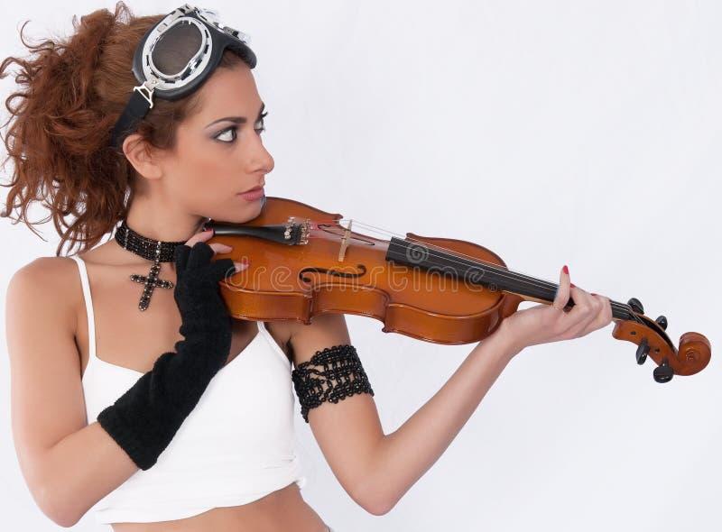 Het meisje van Steampunk met beschermende brillen en viool die ahe eruit ziet royalty-vrije stock foto's