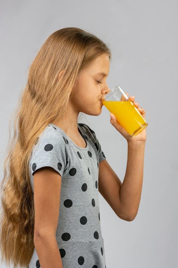 Het meisje van tien jaar drinkt sap, profielmening royalty-vrije stock fotografie