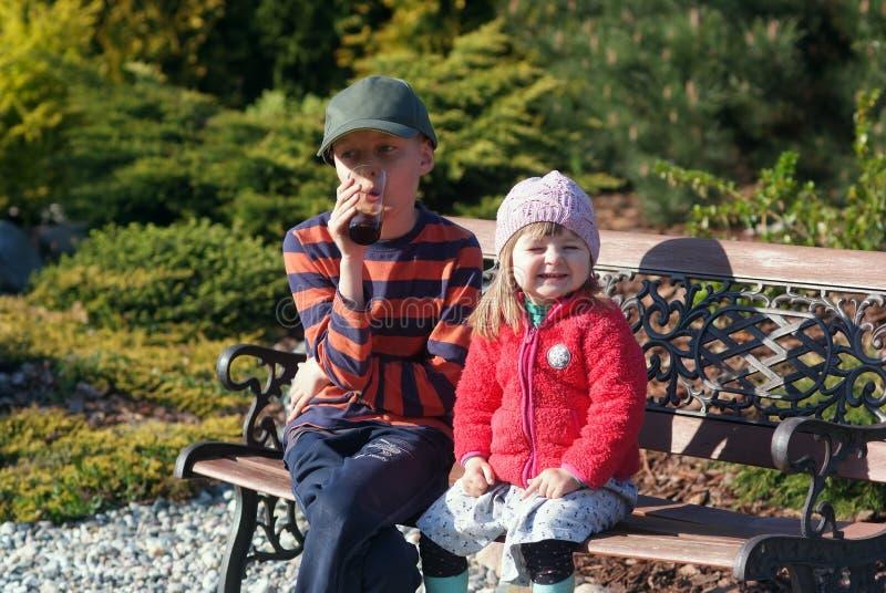 Het meisje van twee jaar met haar broer in de tuin stock fotografie
