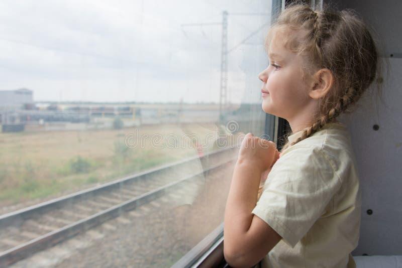 Het meisje van vier jaar kijkt uit het venster van de treinauto stock foto