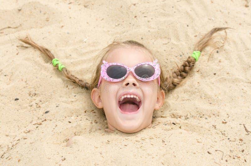 Het meisje van vijf jaar die met glazen op een strand op zijn hoofd in het zand wordt uitgestrooid stock foto