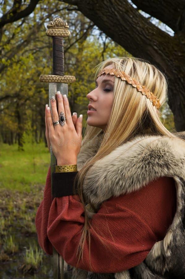 Het meisje van Viking met zwaard in een hout royalty-vrije stock afbeelding