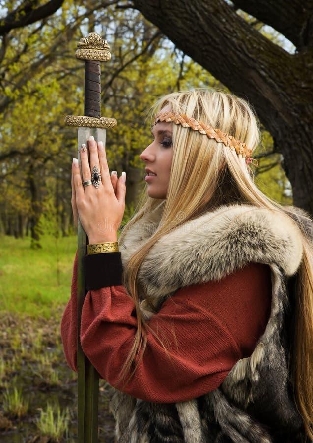 Het meisje van Viking met zwaard in een hout stock foto