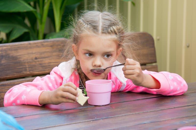 Het meisje van zes jaar drinkt thee van een lepelontbijt op de veranda stock afbeelding