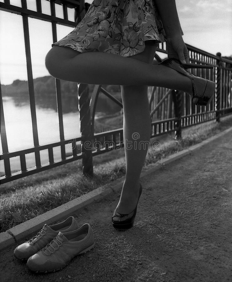 Het meisje verandert high-heeled schoenen in sportenschoenen royalty-vrije stock foto
