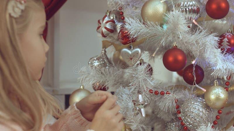 Het meisje verfraait de Kerstboom met speelgoed royalty-vrije stock afbeeldingen