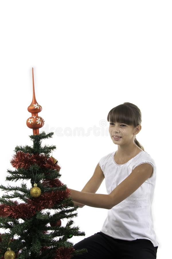Het meisje verfraait een boom van het Nieuwjaar
