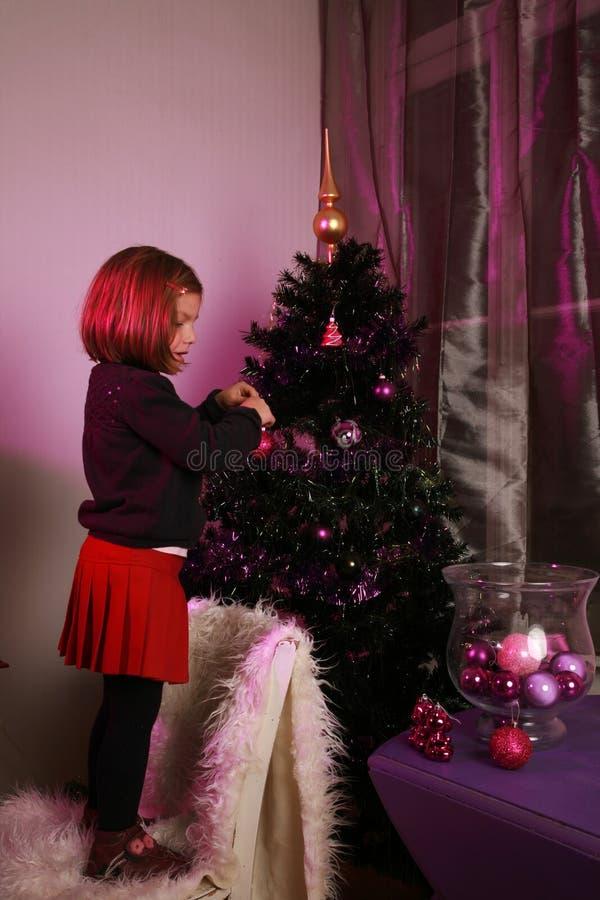 Het meisje verfraait Kerstmisboom stock foto