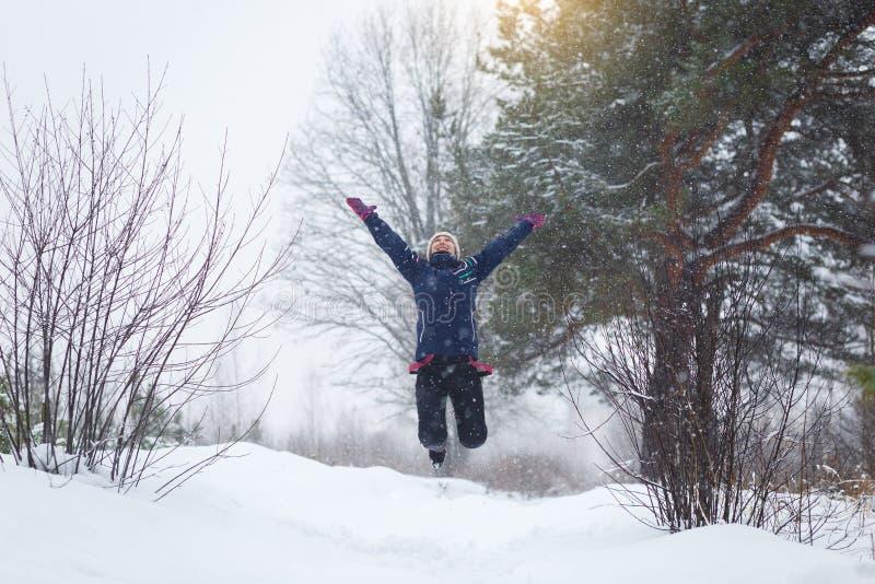 Het meisje verheugt zich in de winter, een meisje die in het de winterbos springen royalty-vrije stock foto's