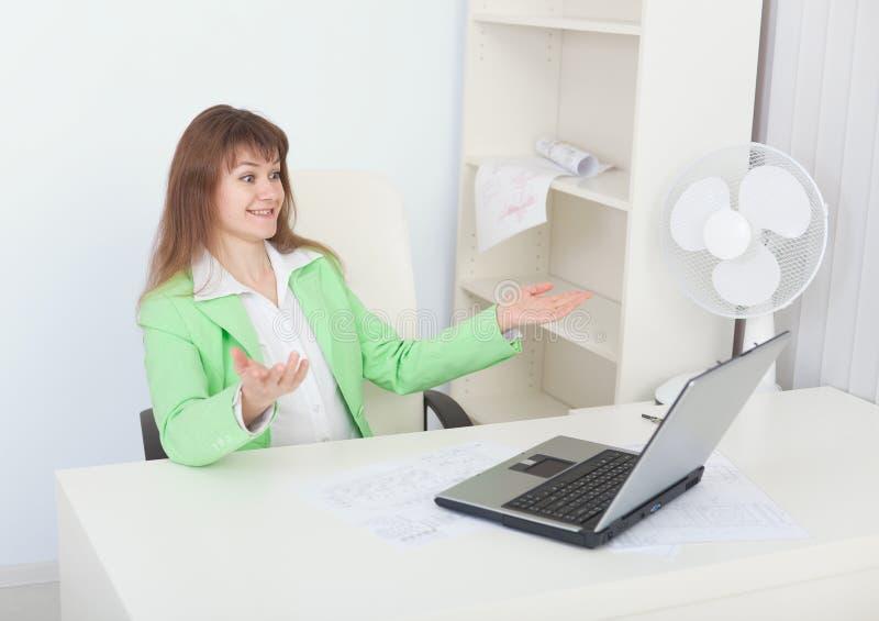 Het meisje verheugt zich zitting in bureau met laptop royalty-vrije stock afbeelding