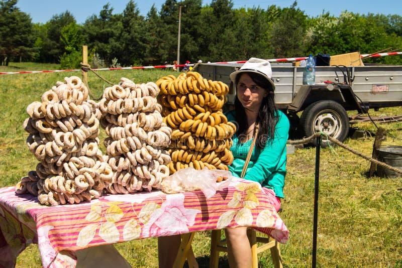 Het meisje verkoopt ongezuurde broodjes tijdens Aardbeifestival stock fotografie