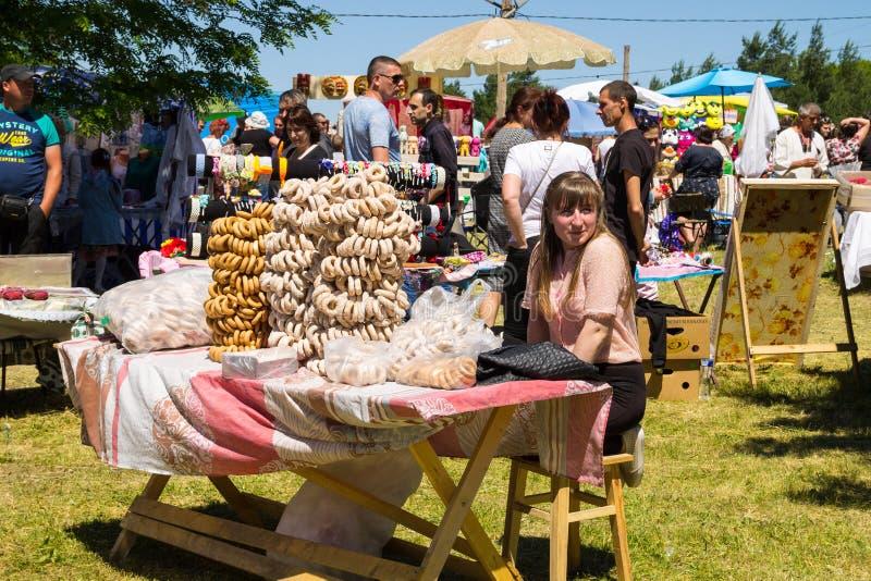Het meisje verkoopt ongezuurde broodjes tijdens Aardbeifestival royalty-vrije stock afbeeldingen