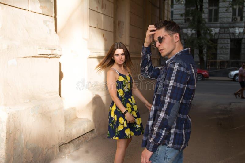 Het meisje verlaat de kerel Gelukkig, houdend van paar, familie de zomermeisje in een kleding een datum in de stad stock fotografie