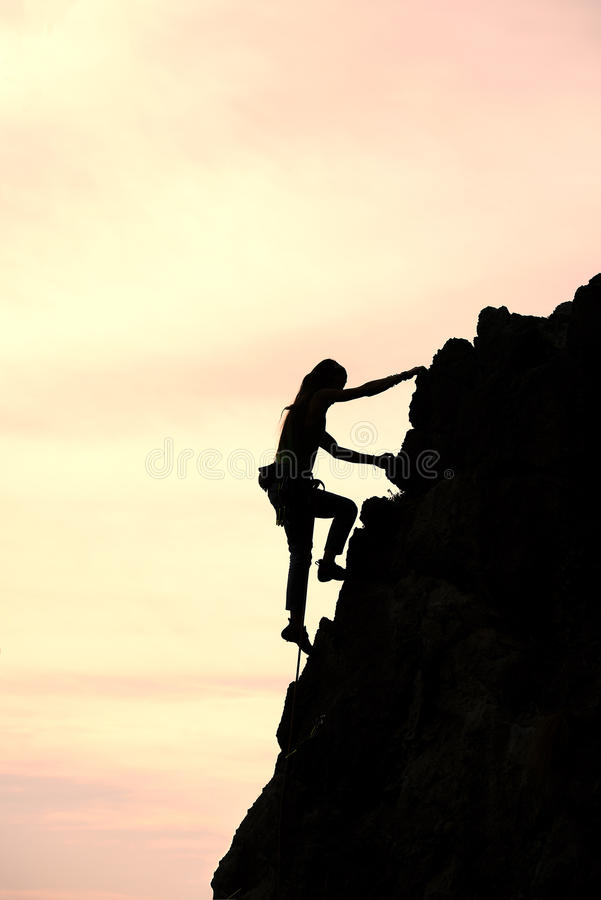 Het meisje verovert alleen de top tijdens een klim in een fantastische moun royalty-vrije stock fotografie