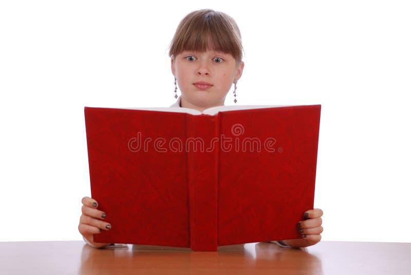 Het meisje is verrast kijkt in het rode boek royalty-vrije stock foto