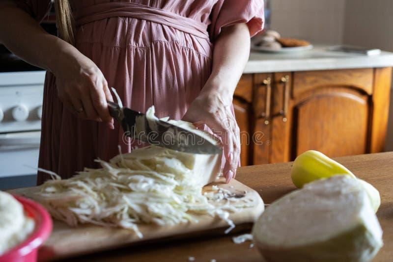 Het meisje verscheurt kool met een mes Keuken het kokende diner sneed groenten Close-up stock foto's